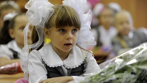 Ein Mädchen sitzt am ersten Schultag in ihrer Klasse.