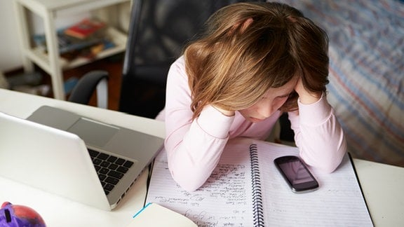 Ein Mädchen schaut auf ein Mobiltelefon, dass auf einem Schulheft liegt