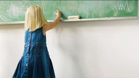 Kleines Mädchen schreibt an einer Schultafel