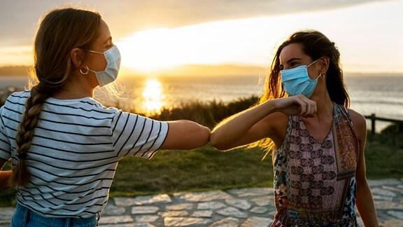 zwei junge Frauen mit Gesichtsmasken berühren sich mit den Ellbögen.
