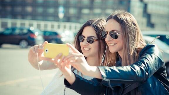Zwei Frauen fotografieren sich mit einem Smartphone selber.