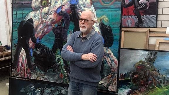 Sighard Gille steht vor einem Gemälde in seinem Atelier
