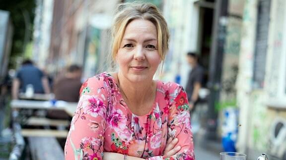 Schriftstellerin Simone Buchholz, in einem Straßencafe sitzend
