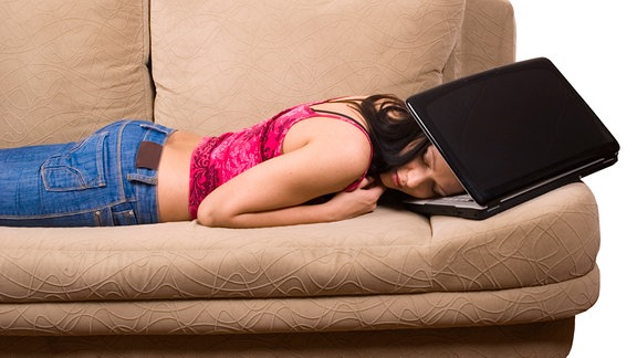Frau liegt auf Sofa, ihren Kopf zwischen Monitor und Tastatur eines Notebooks gesteckt