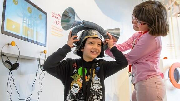 Ein Junge probiert einen ungewöhnlichen Hut an.
