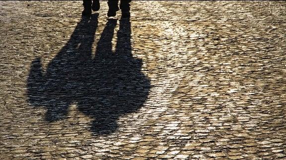 Schatten von zwei Spaziergängern.