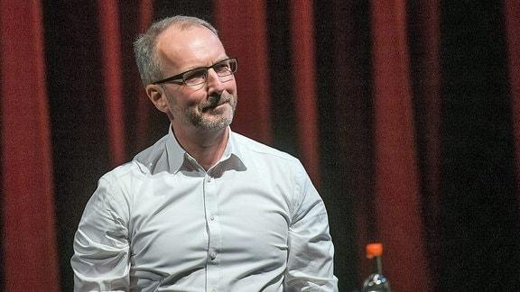 Stefan Schwarz. Ein Mann sitzt während einer Lesung auf einer Bühne und schaut lächelnd ins Publikum.