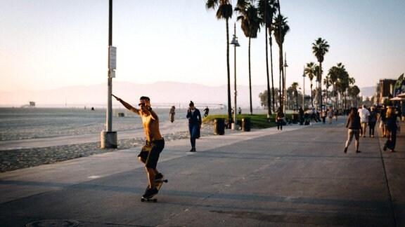 Ein Mann fährt bei Sonnenschein auf einem Strand-Boulevard Skateboard.