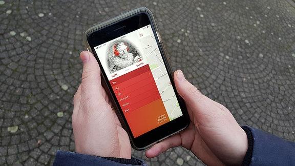 Auf einem Smartphone ist eine App mit dem Portrait des Komponisten Heinrich Schütz aufgerufen