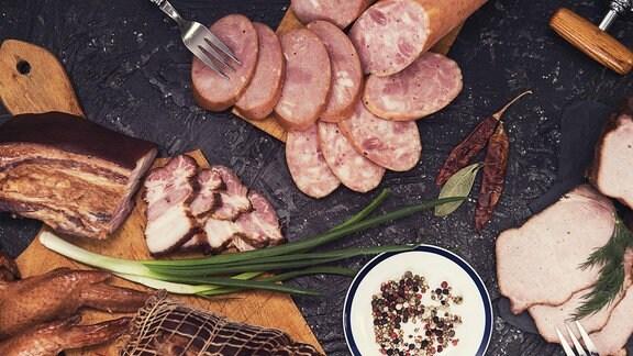 Eine Auswahl an derbem Fleisch und Wurst auf einer Steinplatte.