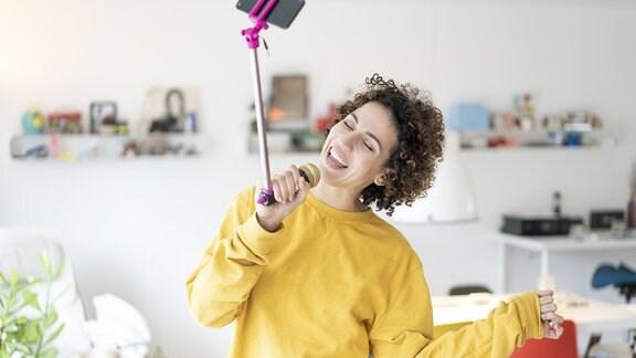 Sorglose Frau singt zu Hause in ein Mikrofon, das an einem Selfie-Stab befestigt ist.