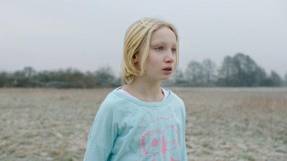 Filmstill, ein blondes Mädchen steht auf einem Feld.