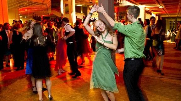 Junges tanzendes Paar beim Abschlussball einer Tanzschule