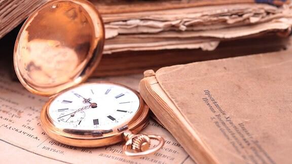 Eine Taschenuhr mit aufgeklapptem Deckel liegt zwischen alten Büchern
