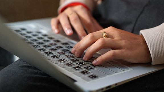 Eine Tastatur ist mit arabischen Schriftzeichen beklebt, jemand tippt darauf