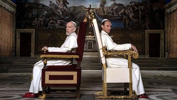 Szene aus der Serie - Zwei Männer sitzen in Stühlen mit dem Rücken zueineinander und schauen zur Kamera.