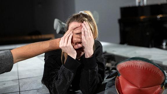 """Ruth, Protagonistin des Theaterstücks """"Monster wie wir"""", verdeckt sich mit den Händen das Gesicht."""