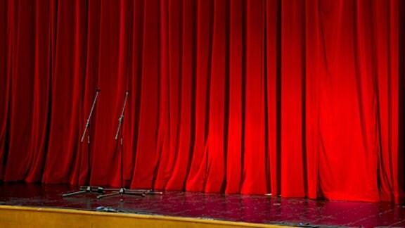 Vor einem roten Theatervorhang  stehen zwei Mikrophone.