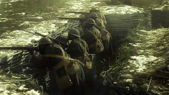 Britische Soldaten stehen mit Gasmasken im Schützengraben.