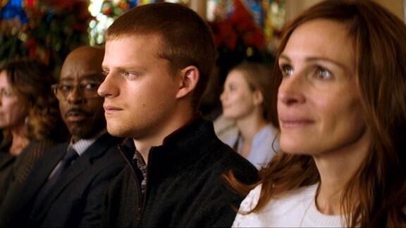 Ein junger Mann sitzt zwischen einer Frau und einem Mann