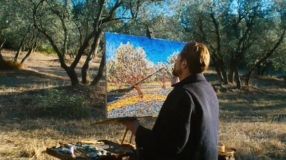 Ein Mann sitzt im freien vor Bäumen und malt dies auf eine Leinwand.