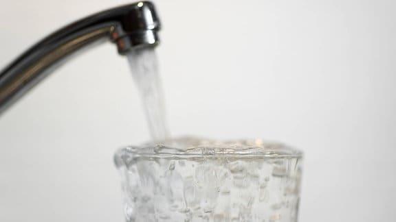 Leitungswasser fließt aus einem Hahn ins Glas
