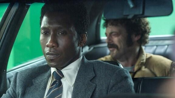 Zwei Männer sitzen in einem Auto.