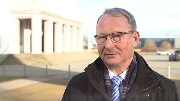 Mann mit Brille (Oberbürgermeister von Bitterfeld-Wolfen Armin Schenk) steht vor dem Kulturpalast Bitterfeld.