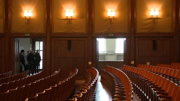 Der große Saal des Kulturpalastes Bitterfeld mit mehreren Stuhlreihen und geöffneten Türen im Hintergrund.