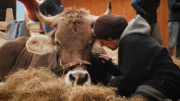 Eine Frau neben einer Kuh