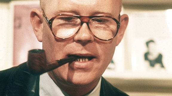 Schriftsteller Uwe Johnson raucht eine Pfeife.