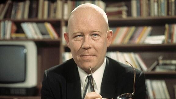 Schriftsteller Uwe Johnson posiert mit Brille in der Hand für ein Photo.