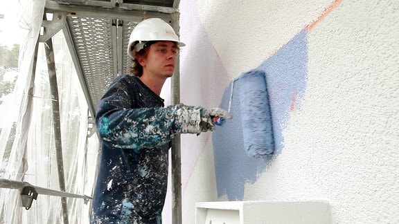 Künstler bemalt Hauswand