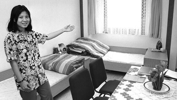 Eine junge vietnamesische Frau in ihrem Zimmer in einem Wohnheim