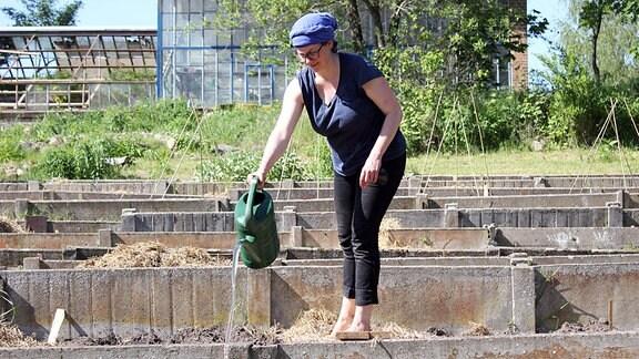 Frau mit Gießkanne in einem Garten