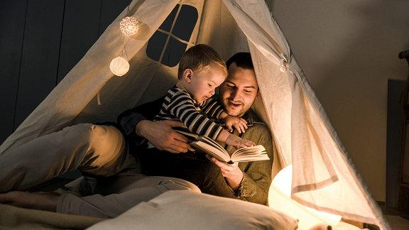 Vater liest seinem Sohn in einem beleuchteten Zelt zu Hause ein Buch vor.