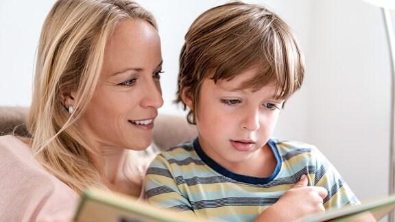 Mutter und Sohn lesen gemeinsam ein Buch auf der Couch zu Hause.