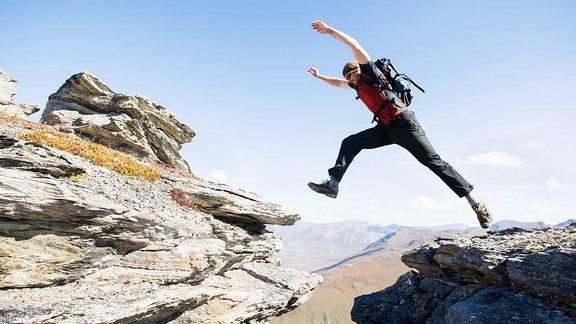 Ein Mann springt über eine Felsspalte.