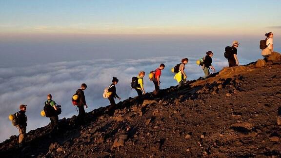Menschen laufen auf einem Vulkan.