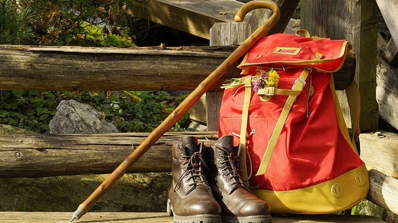 Rucksack mit Wanderstock und Wanderstiefeln auf einer Bank in den Bergen.