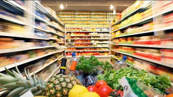 Voller Einkaufswagen zwischen Supermarktregalen