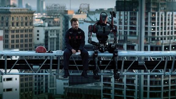 Mann und Roboter sitzen auf einem Stahlgerüst
