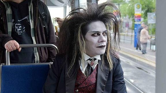 Ein weiß geschminkter Mann in schwarzer Gewandung sitzt in eine Straßenbahn und schaut aus dem Fenster.