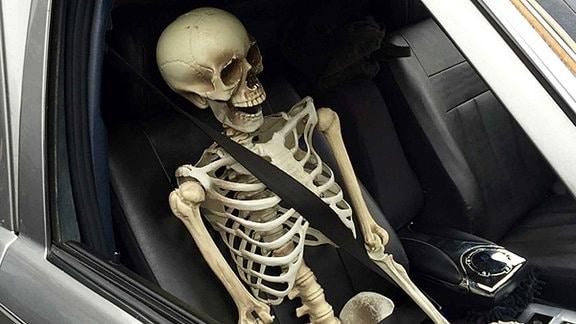 Ein Skelett sitz vorschriftsgemäß angeschnallt auf dem Beifahrersitz eines Autos.