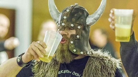 Ein Fan im Wikingerkostüm trinkt Bier bei einem Konzert.