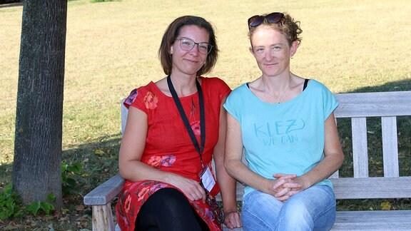 Zwei junge Frauen sitzen in einem Park auf einer Bank.