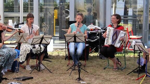 Mehrer Menschen sitzen mit Instrumenten im Freien vor Notenständern und musizieren.