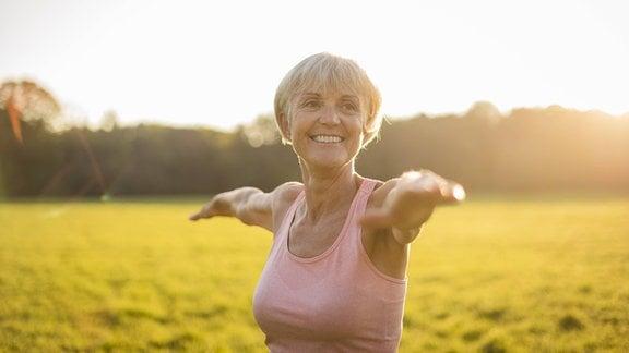 Lächelnde Seniorin praktiziert Yoga auf einer Wiese.