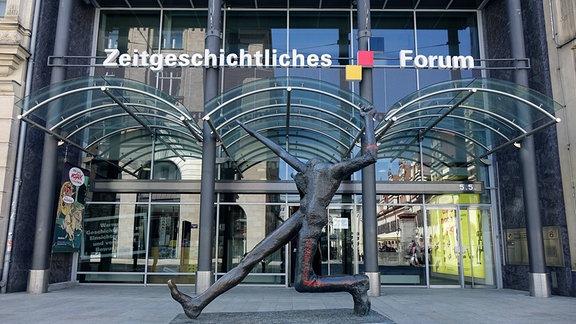 Vor dem Zeitgeschichtlichen Forum in Leipzig steht die Plastik Der Jahrhundertschritt von Wolfgang Mattheuer