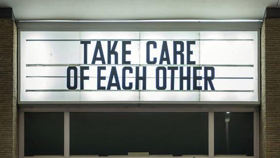 Der Schriftzug Take care of each other steht an der Fassade eines Kinos
